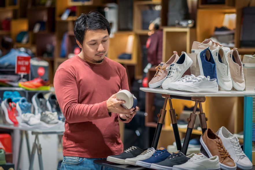 Man shopping for shoes in retail store